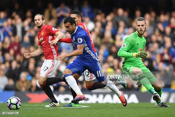 Pedro of Chelsea takes the ball around David De Gea of Manchester United as he scores his sides first goal during the Premier League match between...