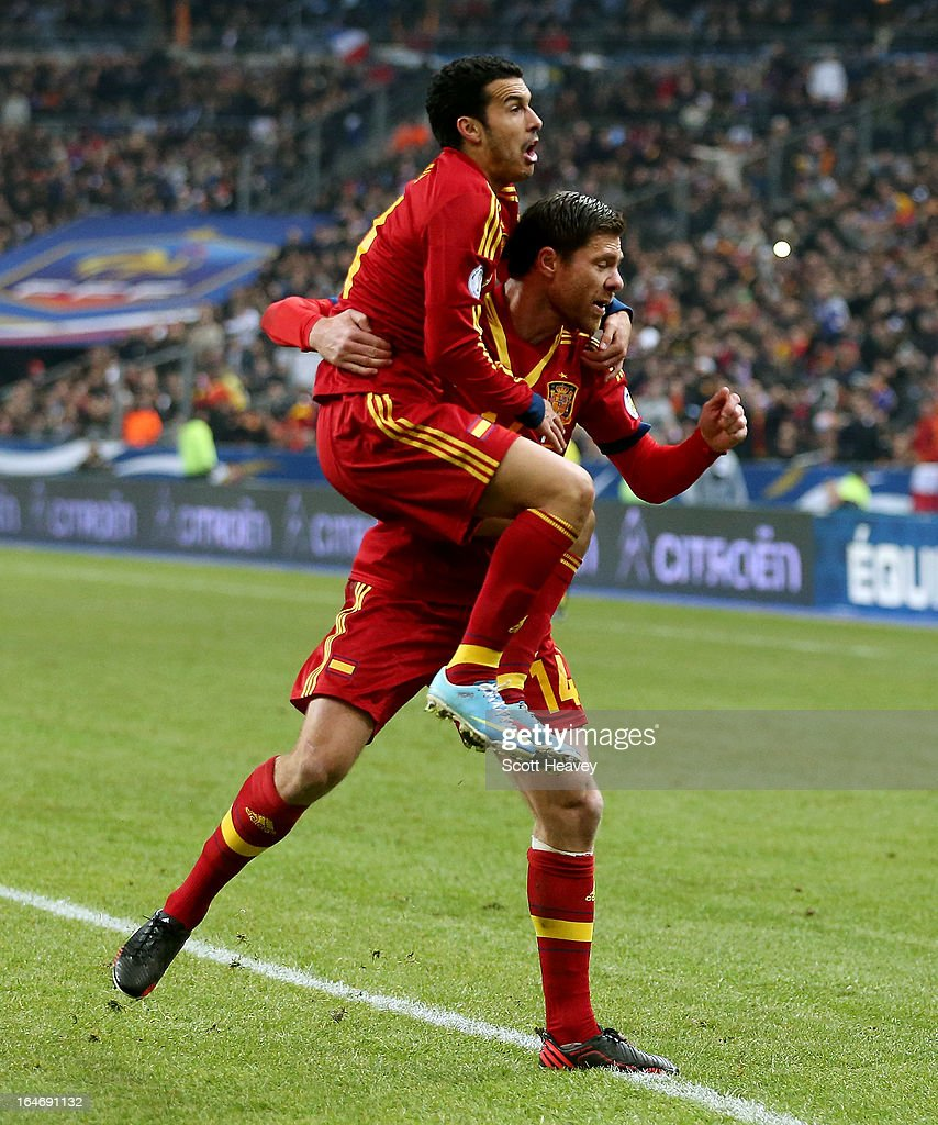 Pedro of Spain celebrates with Xavi Alonso after scoring their first goal during a FIFA 2014 World Cup Qualifier between France and Spain at Stade de France on March 26, 2013 in Paris, France.