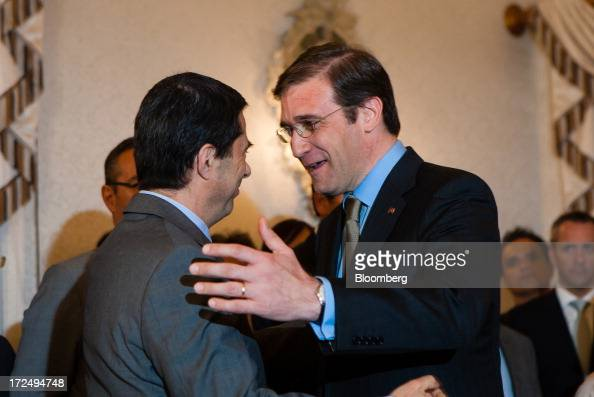 Pedro Passos Coelho Portugal's prime minister right greats Vitor Gaspar former finance minister during a swearing in ceremony for new government...