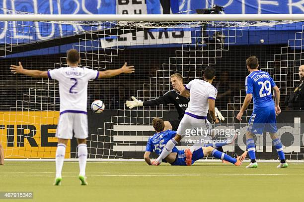 Pedro Ribeiro of Orlando City SC scores on goalkeeper Eric Kronberg of Montreal Impact during the MLS game at the Olympic Stadium on March 28 2015 in...