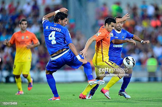 Pedro Rodriguez Ledesma of FC Barcelona duels for the ball with Miguel Torres and Diego Castro of Getafe CF during the La Liga match between Getafe...