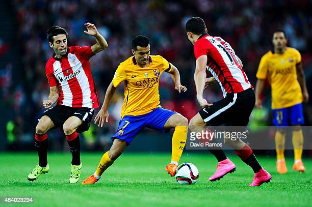 Pedro Rodriguez of FC Barcelona competes for the ball with Markel Susaeta and Oscar de Marcos of Athletic Club during the Spanish Super Cup first leg...