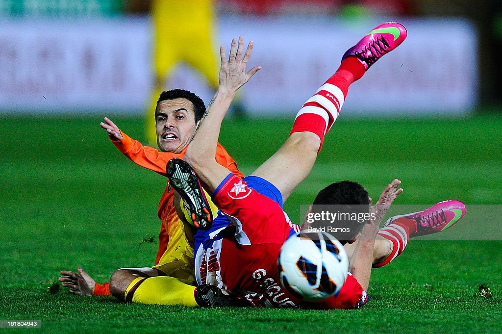 Pedro Rodriguez of FC Barcelona is brought down by Guilherme Siqueira of Granada CF during the La Liga match between Granada CF and FC Barcelona at Estadio Nuevo Los Carmenes on February 16, 2013 in Granada, Spain.
