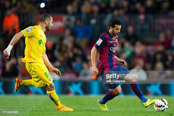 Pedro Rodriguez of FC Barcelona makes a pass beside Mehdi Lacen of Getafe CF during the La Liga match between FC Barcelona and Getafe CF at Camp Nou...