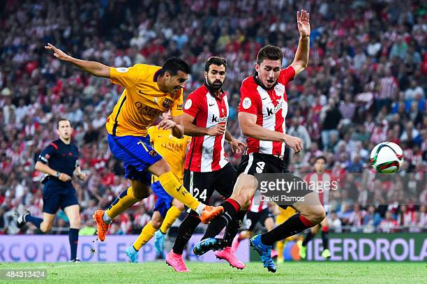 Pedro Rodriguez of FC Barcelona shoots towards goal under a challenge by Aymeric Laporte of Athletic Club during the Spanish Super Cup first leg...