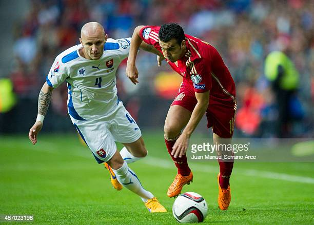 Pedro Rodriguez of Spain duels for the ball with Lukas Tesak of Slovakia during the Spain v Slovakia EURO 2016 Qualifier at Carlos Tartiere on...