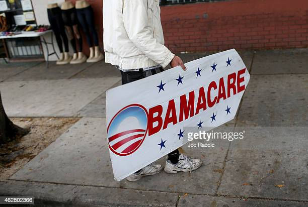 Pedro Rojas holds a sign directing people to an insurance company where they can sign up for the Affordable Care Act also known as Obamacare before...
