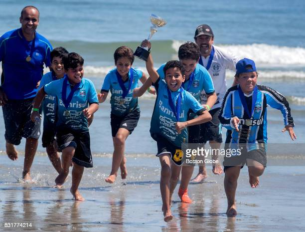 Pedro Vidal holds the trophy as the Gremio USA team celebrates their championship during the Boston Beach Soccer Tournament Series at Nantasket Beach...