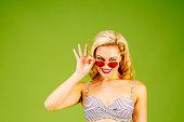 Peeking over red sunglasses, blonde girl in bikini, isolated on green studio background