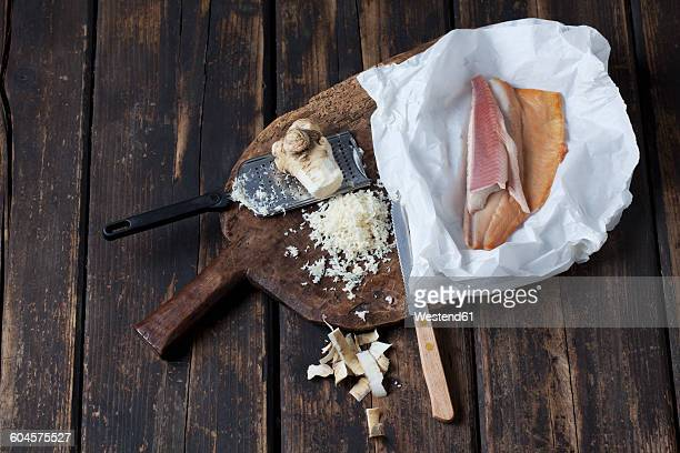Peeled and grated horseradish and greaseproof paper with smoked trout filets on wooden board