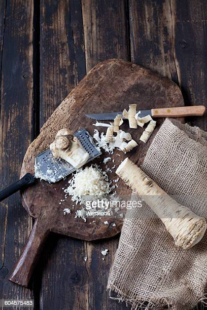 Peeled and grated horseradish on wooden board