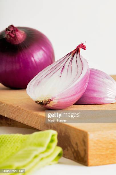 Peeled and halved red onion on chopping board, close-up