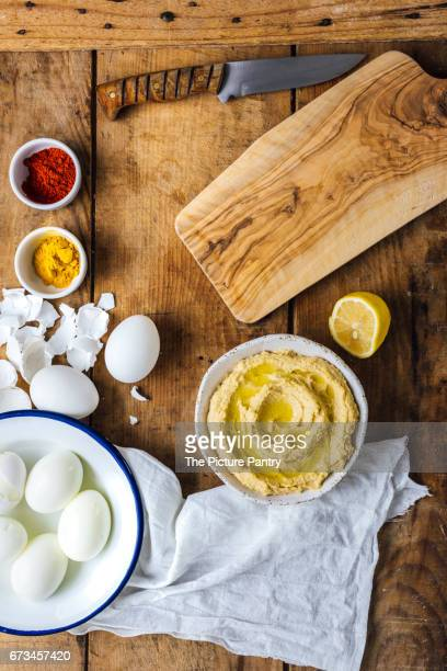 Peeled hard-boiled eggs in a bowl are ready to be sliced and filled with hummus. A bowl of hummus, turmeric and chili powder accompany.