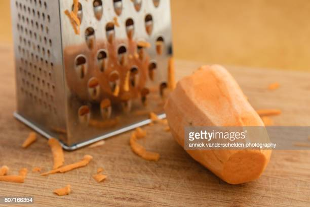 Peeled sweet potato and kitchen grater.