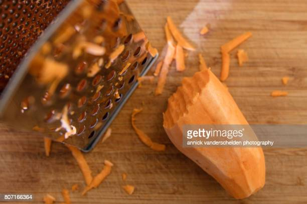 Peeled sweet potato, grated sweet potato and kitchen grater.