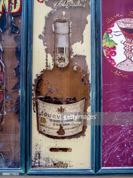A peeling vintage signboard featuring Courvoisier brandy appears outside a cafe in Nice France