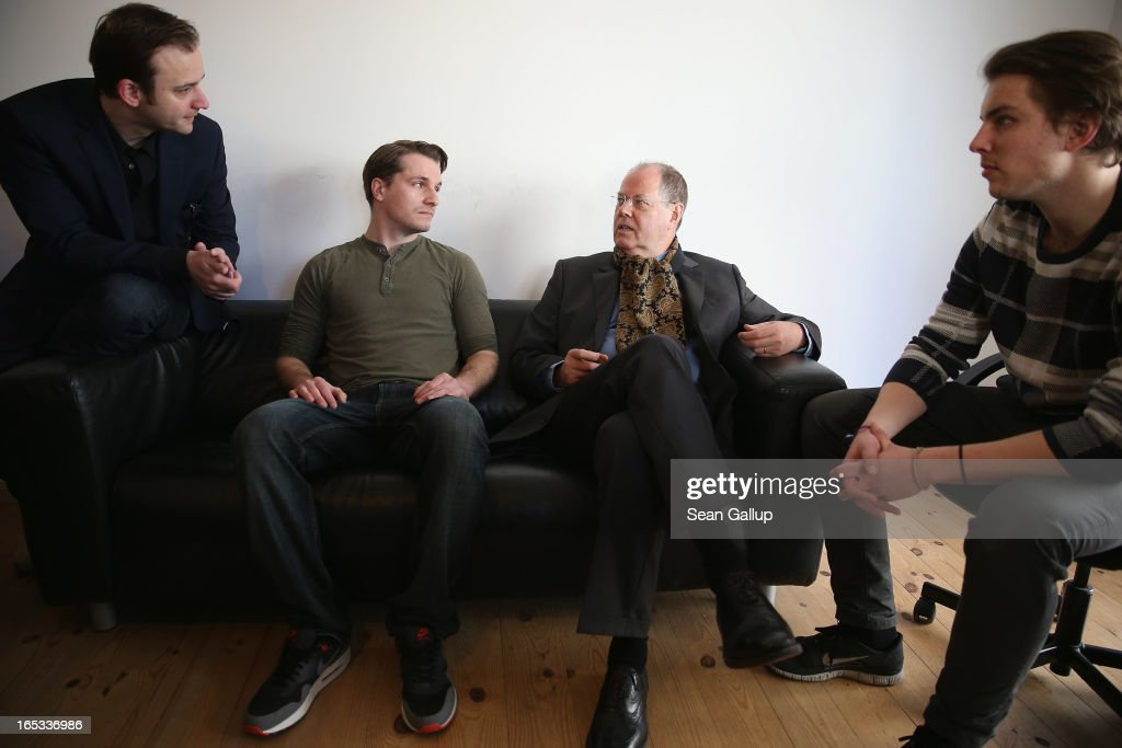 Peer Steinbrueck (3rd from L), candidate for chancellor of the German Social Democrats (SPD), chats with apps developer Mentor employees Simon Schaefer (L) and Lucas Kempfmann (R) at the 'Factory,' a center of Internet start-ups, during a tour of enterprises in Berlin on April 3, 2013 in Berlin, Germany. Steinbrueck will challenge German Chancellor Angela Merkel in federal elections scheduled for September, though so far he is trailing significantly in polls.