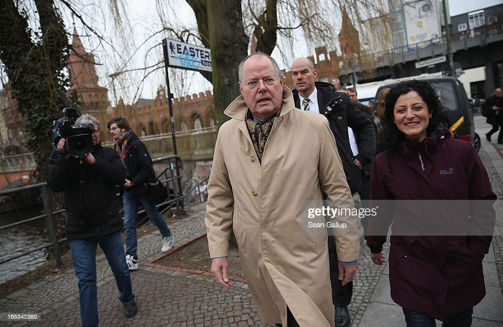 Peer Steinbrueck, candidate for chancellor of the German Social Democrats (SPD), walks near Oberbaumbruecke bridge with local SPD candidate Cansel Kiziltepe (R) during a tour of enterprises in Berlin on April 3, 2013 in Berlin, Germany. Steinbrueck will challenge German Chancellor Angela Merkel in federal elections scheduled for September, though so far he is trailing significantly in polls.
