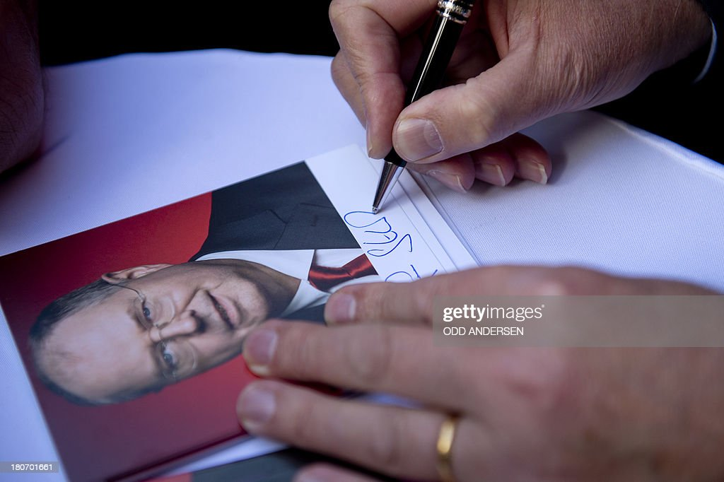 Peer Steinbrueck, Chancellor candidate of the German Social Democrat party (SPD), signs an autograph on a portrait of him for a well-wisher while canvassing in the pedestrian shopping area of the central German town of Peine on September 16, 2013. German voters go to the polls on September 22, 2013 for the general elections.