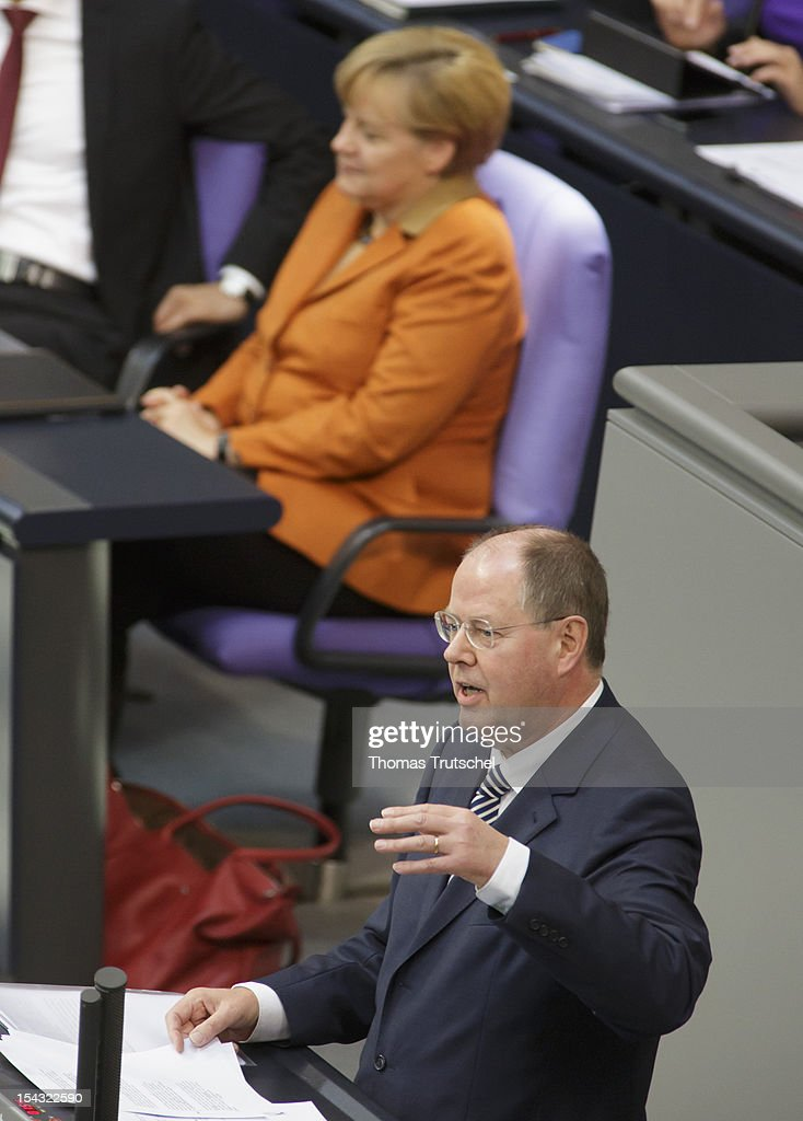 <a gi-track='captionPersonalityLinkClicked' href=/galleries/search?phrase=Peer+Steinbrueck&family=editorial&specificpeople=209110 ng-click='$event.stopPropagation()'>Peer Steinbrueck</a>, Chancellor candidate of the German Social Democrats (SPD) for the 2013 general election speak at Reichstag, the seat of the German Parliament (Bundestag), on October 18, 2012 in Berlin, Germany. In Background: German Chancellor <a gi-track='captionPersonalityLinkClicked' href=/galleries/search?phrase=Angela+Merkel&family=editorial&specificpeople=202161 ng-click='$event.stopPropagation()'>Angela Merkel</a>.