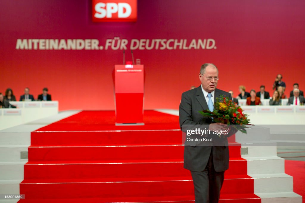 <a gi-track='captionPersonalityLinkClicked' href=/galleries/search?phrase=Peer+Steinbrueck&family=editorial&specificpeople=209110 ng-click='$event.stopPropagation()'>Peer Steinbrueck</a>, chancellor candidate of the German Social Democrats (SPD), holds flowers in the hand at the the SPD federal party convention on December 9, 2012 in Hanover, Germany. The SPD is convening to set its policy course for the next year and to celebrate Steinbrueck, who will run for chancellor in elections set for 2013.