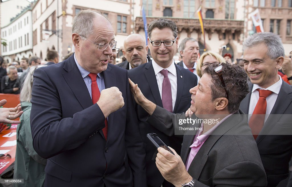 <a gi-track='captionPersonalityLinkClicked' href=/galleries/search?phrase=Peer+Steinbrueck&family=editorial&specificpeople=209110 ng-click='$event.stopPropagation()'>Peer Steinbrueck</a> (L), chancellor candidate of the German Social Democrats, SPD's candidate in Hesse, Thorsten Schaefer Guembel (C) and Mayer of Frankfurt, Peter Feldmann, meet with a supporter during a campaign event on September 21, 2013 on Roemer place in Frankfurt am Main, Germany. Germany is facing federal elections scheduled for September 22 and a wide spectrum of political parties is vying for votes.