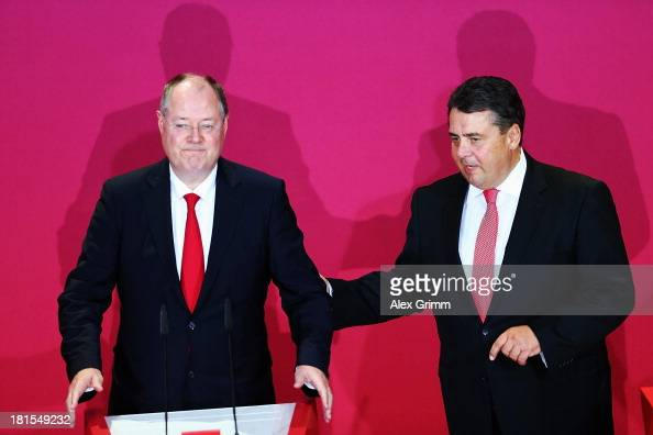 Peer Steinbrueck chancellor candidate of the German Social Democrats and chairman Sigmar Gabriel react after initial exit poll results give the party...