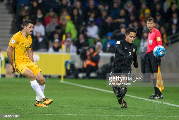 Peerapat Notchaiya of the Thailand National Football Team passes the ball down field in front of Tom Rogic of the Australian National Football Team...