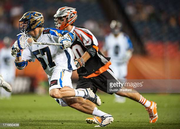 Peet Poillon of the Charlotte Hounds drives past Jeremy Sieverts of the Denver Outlaws during a Major League Lacrosse game at Sports Authority Field...