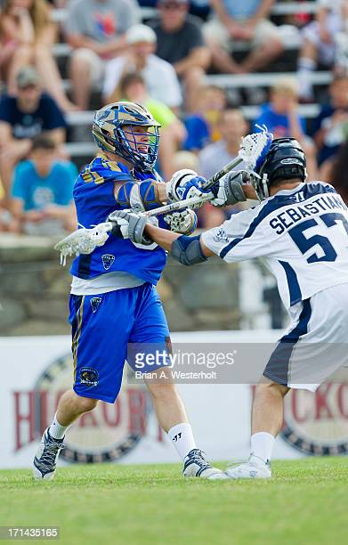 Peet Poillon of the Charlotte Hounds follows through on a shot on goal as he is checked by Domenic Sebastiani of the Chesapeake Bayhawks at American...