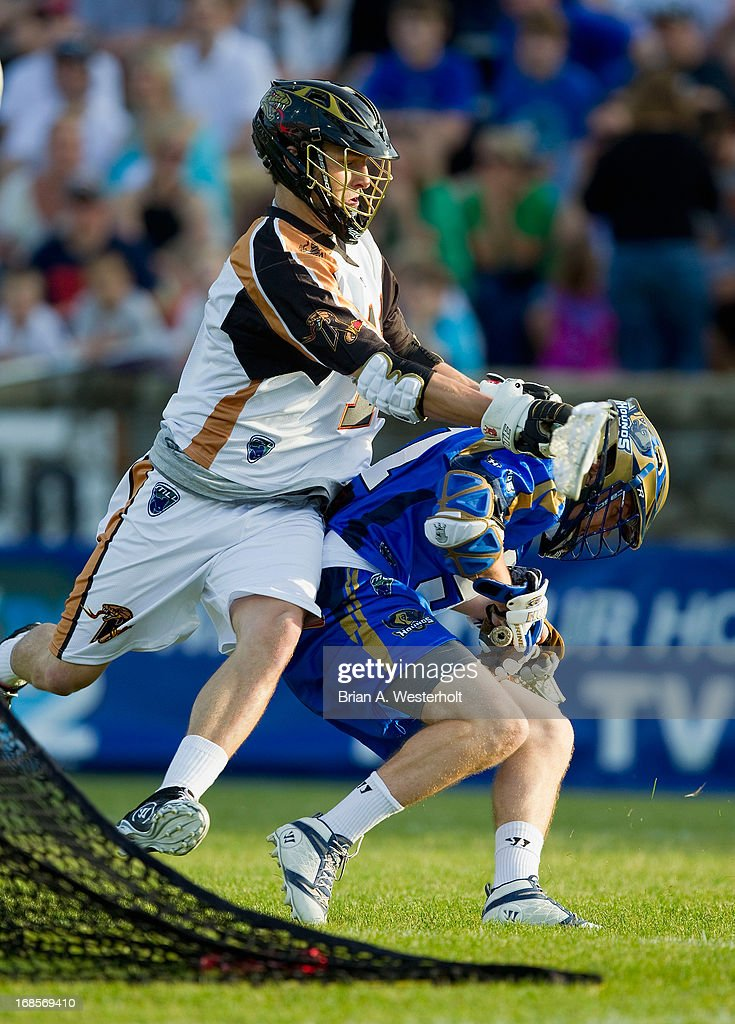 Peet Poillon #57 of the Charlotte Hounds is cross checked by Joel White #11 of the Rochester Rattlers during first half action at American Legion Memorial Stadium on May 11, 2013 in Charlotte, North Carolina.