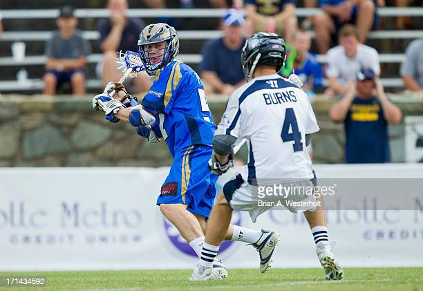 Peet Poillon of the Charlotte Hounds keeps the ball away from Dan Burns of the Chesapeake Bayhawks at American Legion Memorial Stadium on June 22...