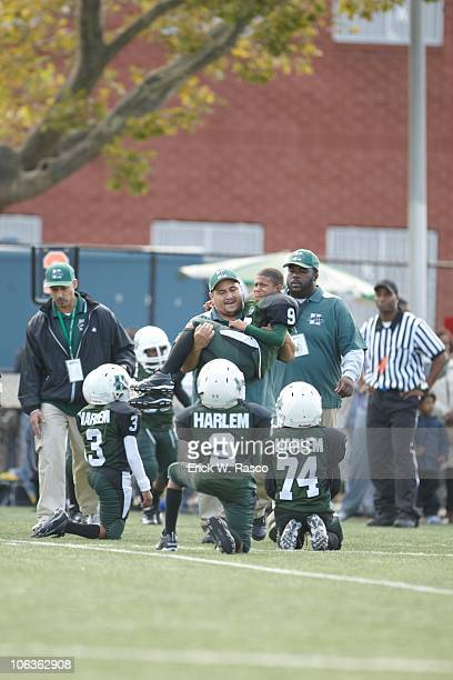 Harlem Jets player getting carried off field by coach after sustaining injury during game vs Mill Basin Mariners at Harlem River Park New York NY...