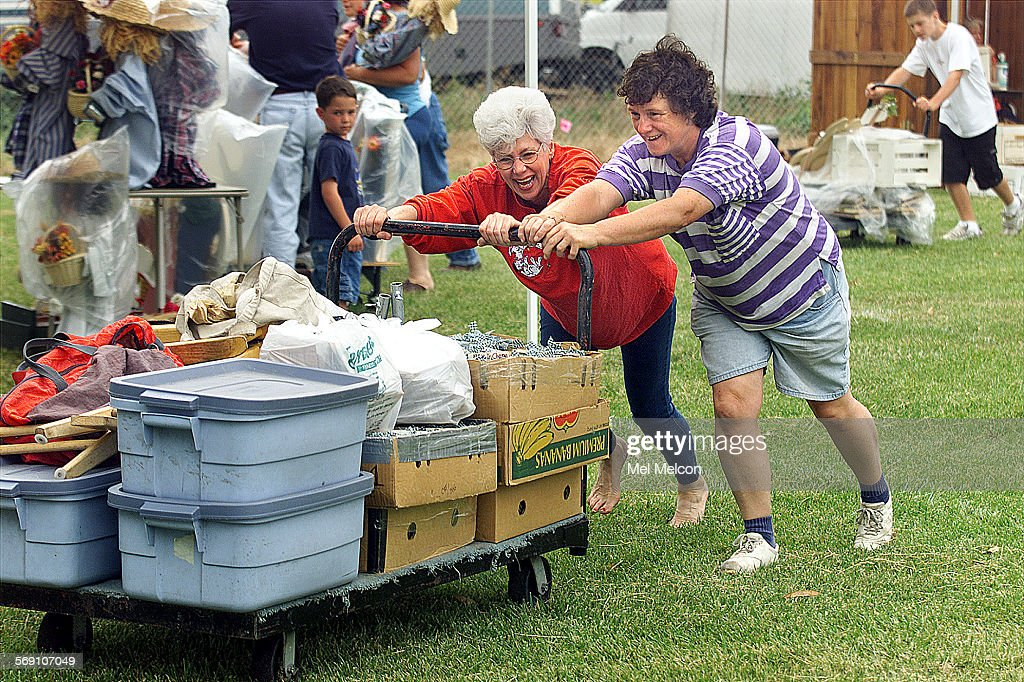 Peg Provansal left gets help from JoAnn Rose as they wheel in display items toward tent where Provansal will be selling whimsical signs during the...