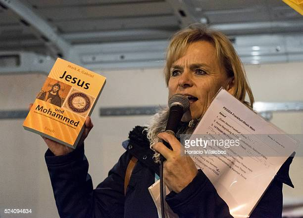 Pegida leader Heidi Mund shows Mark Gabriel book on Jesus and Muhammad while addressing some 30 pro Pegida participants surrounded by police officers...