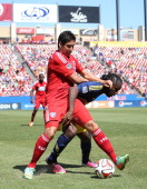 Peguy Luyindula defends the ball against David Texeira of FC Dallas at Toyota Stadium in Frisco on May 4 2014 in Frisco Texas