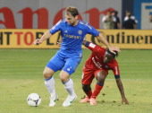 Peguy Luyindula of Paris Saint Germain defends against Branislav Ivanovic of Chelsea FC as he plays the ball during the match at Yankee Stadium on...