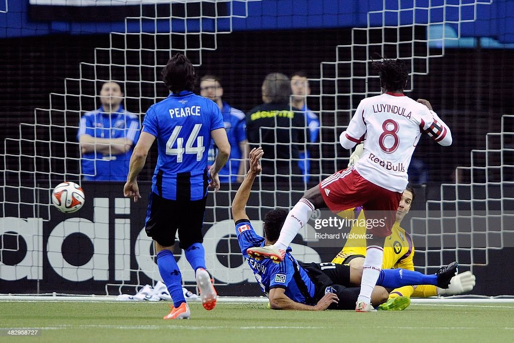 Peguy Luyindula #8 of the New York RedBulls kicks the ball past Troy Perkins #1 of the Montreal Impact to score during the first half of the MLS game at the Olympic Stadium on April 5, 2014 in Montreal, Quebec, Canada.
