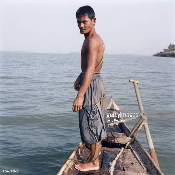 Peh prepares to jump into the Mekong River near Phnom Penh While breathing through the hose wrapped around his waist he will untangle a fishing net...