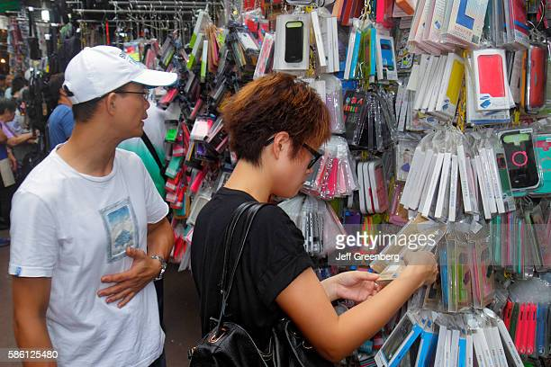Pei Ho Street market Asian couple looking at smartphone protective covers