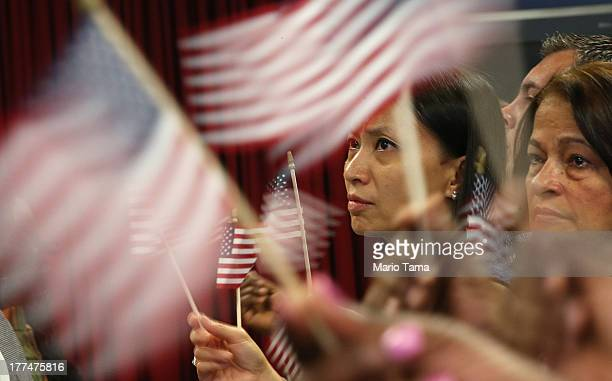 Pei Lin Kuo waves an American flag with other citizenship candidates at a naturalization ceremony for approximately 150 citizenship candidates at...