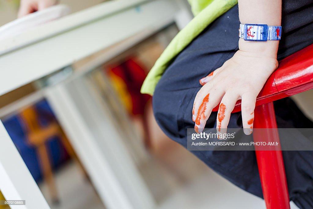 Peinture orange sur les doigts