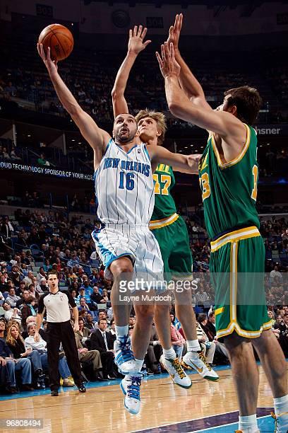 Peja Stojakovic of the New Orleans Hornets shoots around Mehmet Okur and Andrei Kirilenko of the Utah Jazz on February 17 2010 at the New Orleans...