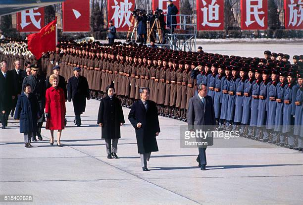 Peking China President Richard Nixon with ChouEnLai review troops of the Red Chinese Army Mrs Nixon also appears in this general view