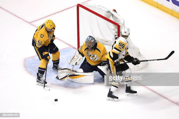 Pekka Rinne and Austin Watson of the Nashville Predators defend Jake Guentzel of the Pittsburgh Penguins during the second period in Game Six of the...