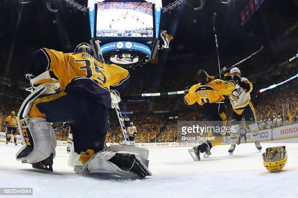 Pekka Rinne looks on as his teammate Ryan Ellis of the Nashville Predators is hit by Jake Guentzel of the Pittsburgh Penguins during the second...