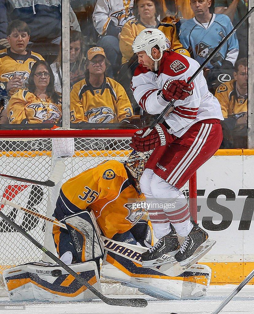 Pekka Rinne of the Nashville Predators blocks a shot against David Moss of the Phoenix Coyotes during an NHL game at Bridgestone Arena on April 10...