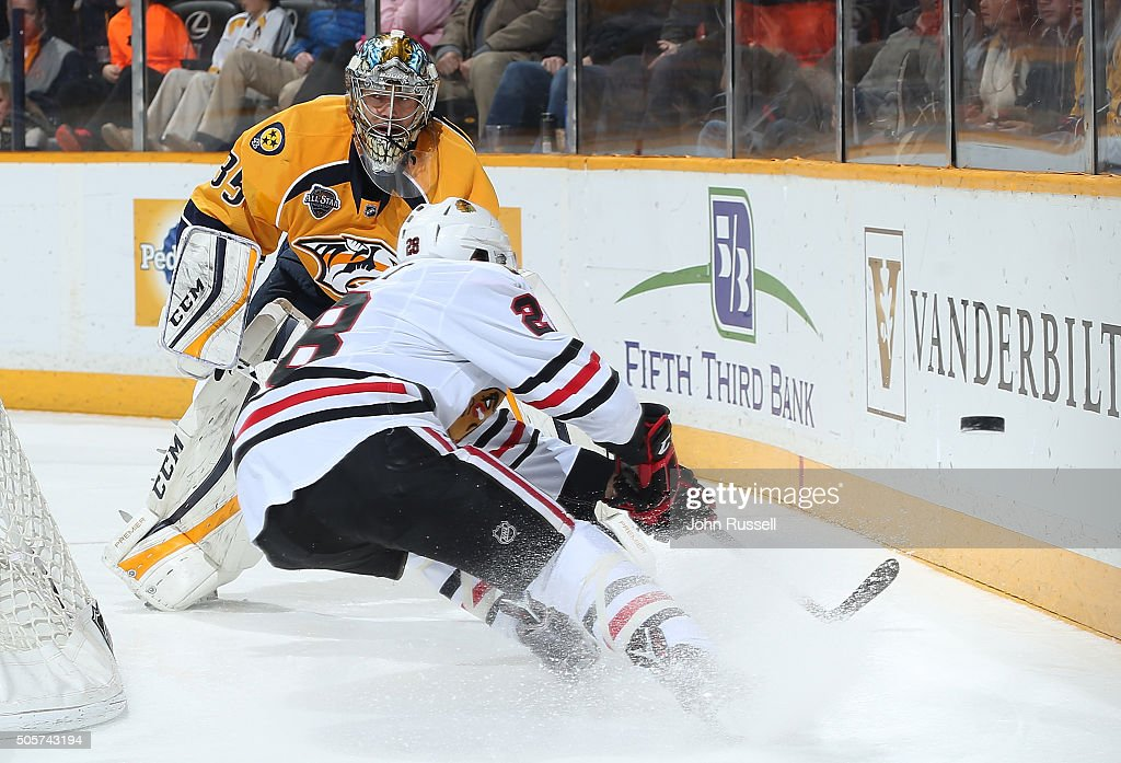 Pekka Rinne #35 of the Nashville Predators clears the puck against Ryan Garbutt #28 of the Chicago Blackhawks during an NHL game at Bridgestone Arena on January 19, 2016 in Nashville, Tennessee.