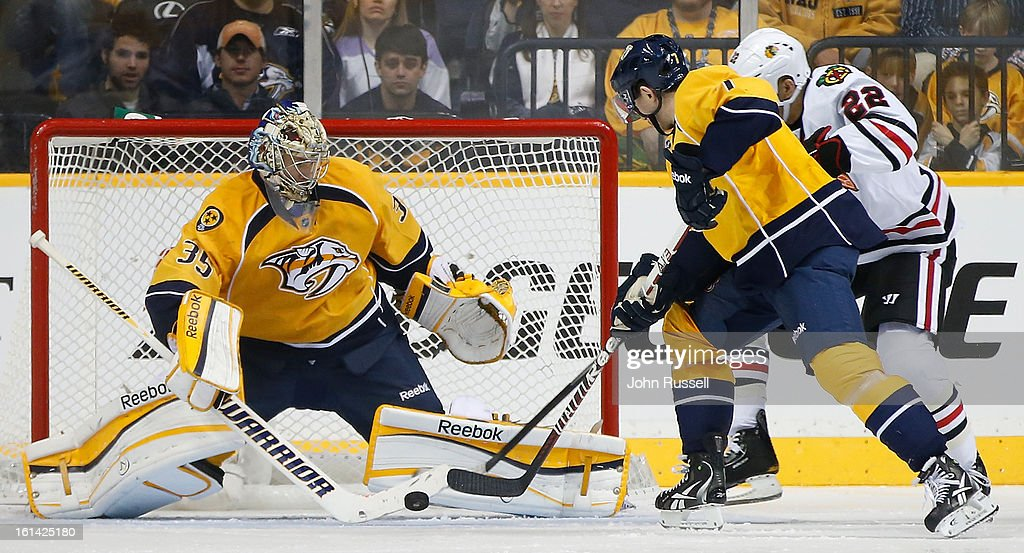<a gi-track='captionPersonalityLinkClicked' href=/galleries/search?phrase=Pekka+Rinne&family=editorial&specificpeople=2118342 ng-click='$event.stopPropagation()'>Pekka Rinne</a> #35 of the Nashville Predators clears the puck from <a gi-track='captionPersonalityLinkClicked' href=/galleries/search?phrase=Jamal+Mayers&family=editorial&specificpeople=213279 ng-click='$event.stopPropagation()'>Jamal Mayers</a> #22 of the Chicago Blackhawks during an NHL game at the Bridgestone Arena on February 10, 2013 in Nashville, Tennessee.