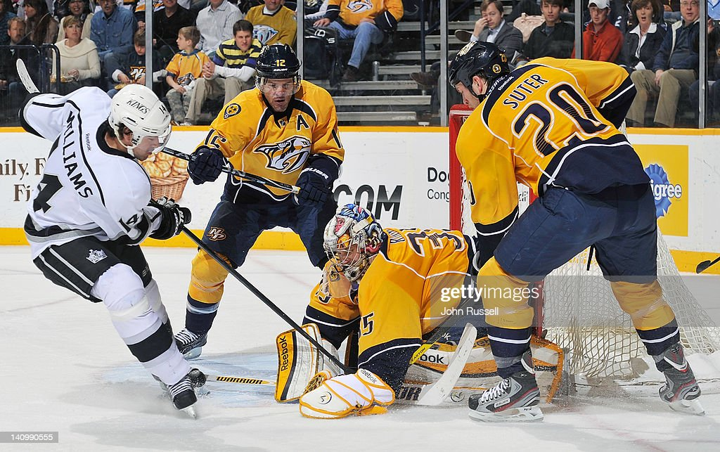 Pekka Rinne of the Nashville Predators covers the puck against Justin Williams of the Los Angeles Kings during an NHL game at the Bridgestone Arena...